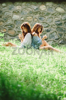 Two Asian Teen Females Relaxing Together in Heavenly Green Meadow, Idyllic Nature Scene