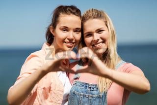 teenage girls or best friends at seaside in summer