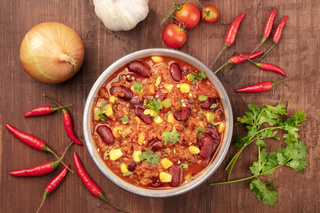 Chili con carne, shot from above on a dark rustic wooden background with ingredients
