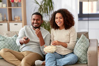 african couple with popcorn watching tv at home