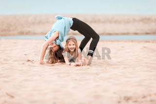 Two young girls doing gymnastics on the beach