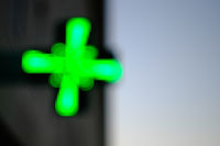 Pharmacy green cross blurred over light and dark background