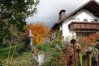 Einfamilienhaus mit Gartenteich im Herbst