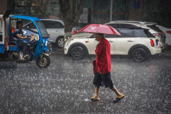 Man walking in tropical monsoon rain