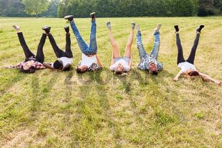 Junge Leute strecken die Beine in die Luft