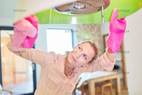 Putzfrau beim Lampe putzen in der Wohnung
