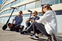 Group of young Caucasian people girl her friend guys in casual clothes seated on electric scooter footboard resting enjoy warm sunny day outdoors. Modern technology eco-friendly device usage concept