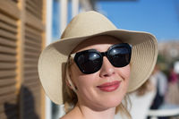 Close up fashion portrait of glamour stylish blonde lady with cool retro sunglasses . The girl sitting in caffe and enjoying time out.