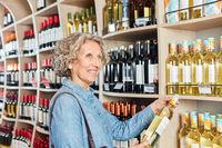 Seniorin mit einer Flasche Weißwein am Weinregal