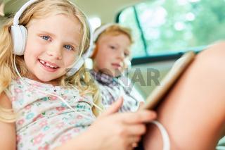 Kinder im Auto hören Musik mit Kopfhörer