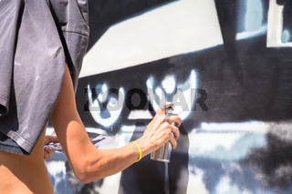 TURIN, ITALY - June 07, 2018: anonymous graffiti artist working on his piece of street art in urban area