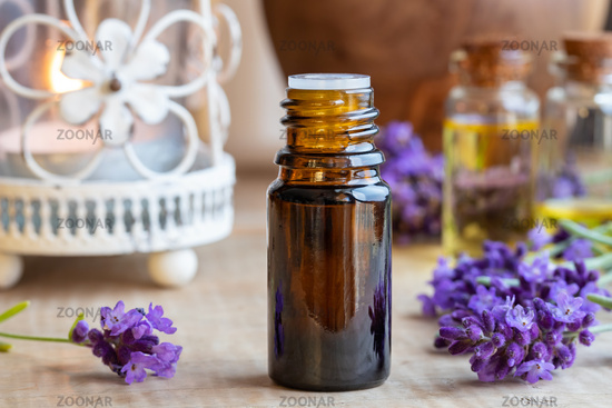A bottle of lavender essential oil with fresh blooming lavender