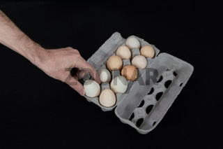 Male hand taking one egg from paper tray on black background