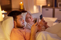 couple using smartphones in bed at night