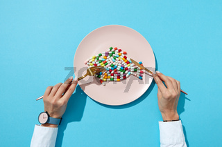 Vitamin pills and tablets in the shape o a fish in a plate and woman's hand with watch on a blue background. Flat lay