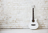 Acoustic white guitar leaning against a white wall in an empty room