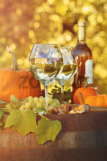 Glasses of white wine with pumpkins on barrel