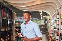 Afrikanischer Mann mit einer Flasche Rotwein