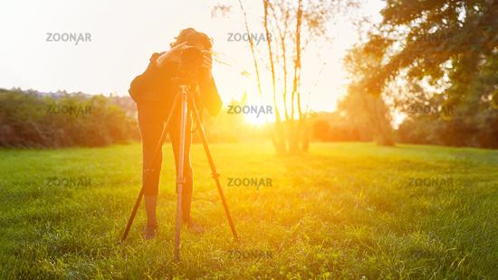 Naturfotograf mit Kamera auf Stativ in Landschaft