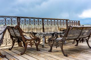 Dekorative Bänke und Schmiedeeisen Zaun am Meer