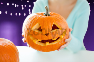 close up of woman with halloween pumpkin