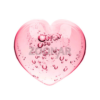 Pink serum gel, heart shape puddle isolated on white backdrop, top view. Squeezed transparent care gel with bubbles close up, macro isolated on white background
