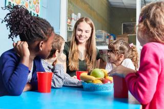 Kinder und Betreuerin essen zusammen Obst