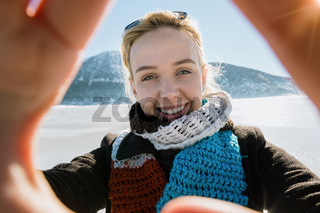 Smiling young woman in coat and scarf taking selfie outdoors in winter