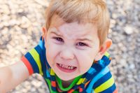 Emotional crying baby face, close up kid