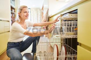Junge Hausfrau beim Geschirrspüler einräumen