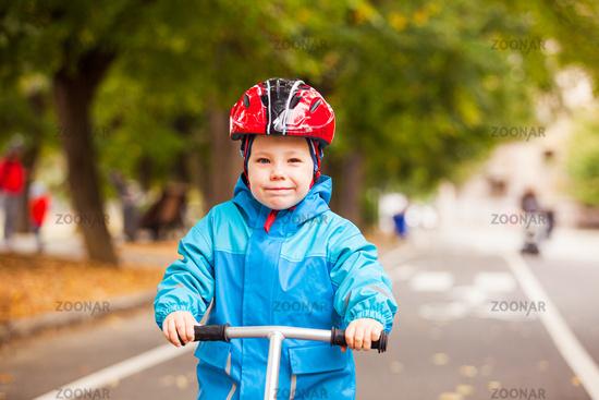 Adorable kid of three years riding on balance bike