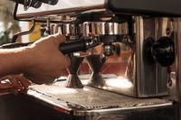 Smallbusines owner preparing espresso using chromed coffee machine