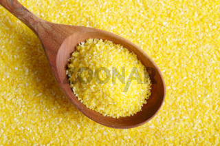 Corn grits yellow background with wooden spoon top view