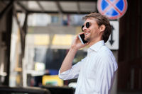 Nice-looking Employee Stands In The Parking Lot And Communicates On A Mobile Device