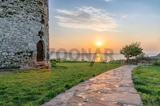 Sun rising from the sea on the Black Sea Coast. Alley at sunrise in Nessebar ancient city with ancient Tower at the left. Nesebar, Nesebr is a UNESCO World Heritage Site. Sunrise in Nessebar, Bulgaria