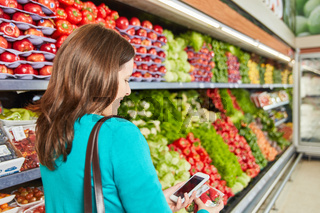 Frau nutzt Barcode Scanner zum Preisvergleich