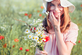 Beautieful young girl in the field of wild flowers