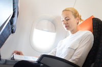 Woman reading in flight magazine on airplane. Female traveler reading seated in passanger cabin. Sun shining trough airplane window