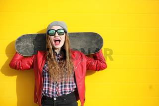 A young hipster girl is riding a skateboard. Girls girlfriends f