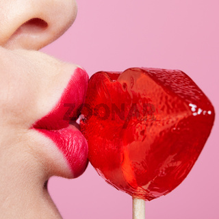Red female lips shape lollipop. Close-up of woman lips kissing candy. Sweet tooth concept