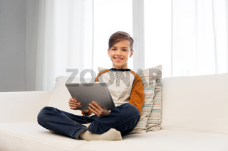 smiling boy with tablet pc computer at home