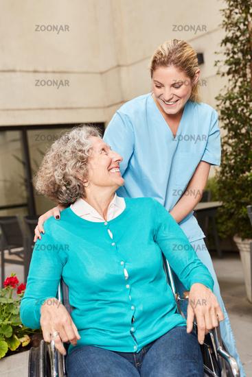 Seniorin im Rollstuhl und Pflegekraft