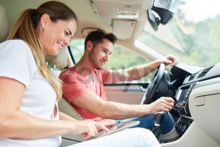 Paar beim Auto fahren mit Tablet Computer