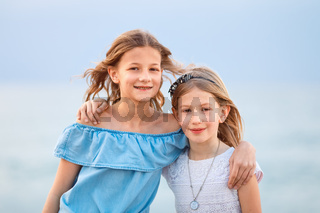 Two young girls wearing casual summer clothing looking, smiling at camera in a coastal region