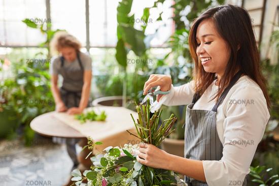 Floristin mit Schere beim Blumenstrauß binden