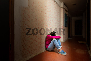 Sad and desperate woman sits in a dark corridor