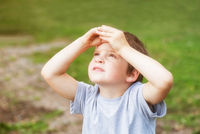 5 years old boy looks at the sky covering his eyes from the sun with his palms