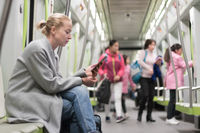 Beautiful blonde woman using smart phone while traveling by metro public transport.