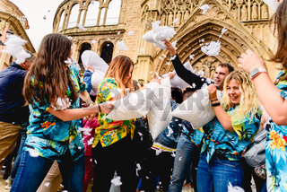 Valencia, Spain - April 6, 2019: Group of young people having fun beating each other with pillows outdoors during a party in a public square of the city.
