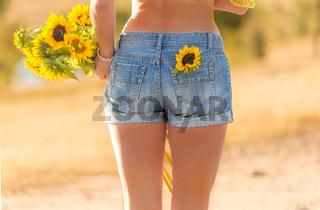 Woman holding sunflowers in warm sunlight